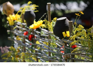 Fence in the village, garden, antique dishes. Poppy Flowers and Wildflowers, sunflower