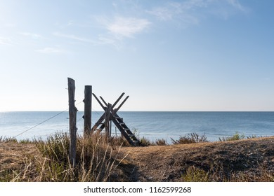 Fence with a wooden stile by the coast of the Swedish island Oland in the Baltic Sea