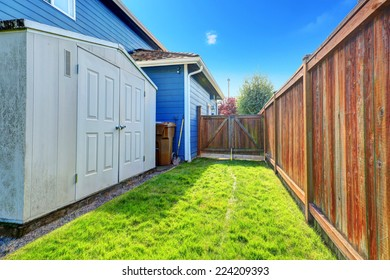 Fenced backyard area with gate. Storage shed with white doors