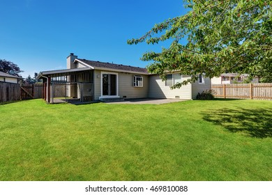Fenced Backyard garden with cage and green grass.  American Rambler house exterior. Northwest, USA