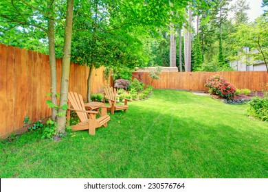 Fenced backyard with green lawn, flower beds and romantic sitting area with wooden chairs and table