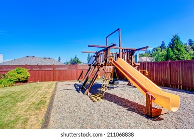 Fenced backyard with lawn and playground for kids.