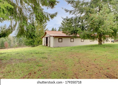 Fenced countryside horse stable barn with fir trees.