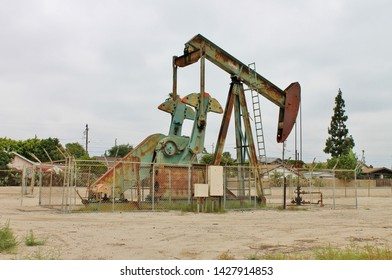 A fenced off Lufkin pumpjack drilling rig in the middle of a residential neigborhood in California