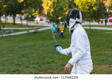 A fencing athlete with blue glove is standing on a green field