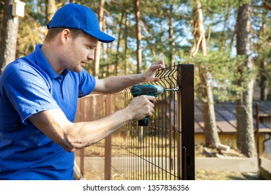 fencing services - worker installing welded metal mesh fence