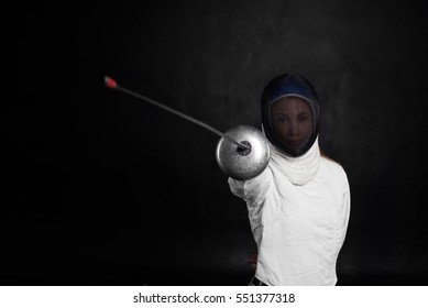 Fencing sport concept. Girl in white costume with sword in one hand on black background. Copy space for advertising goods or text