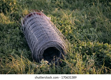 Fencing wire in a roll, lying on its side in clover and pasture grass, waiting to be put up for a horse fence.