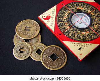Feng shui compass (Luopan) and chinese coins on black background