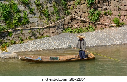 FENGHUANG - April 13:man collect rubbit in the river at Fenghuang ancient town on April 13, 2015 in Fenghuang,China.Fenghuang ancient town was added to UNESCO World Heritage Tentative List.