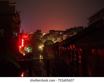 Fenghuang, China - 16 October, 2016: The atmospheric  old town of Fenghuang, in Hunan province. Neon lights illuminate the sky above a narrow river.