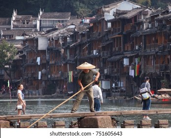Fenghuang, China - 17 October, 2016: A local fisherman in a traditional wicker hat works on the river crossing in the old town of Fenghuang, Hunan province,