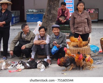 Fenghuang, China - 18 October, 2016: Happy friends and family at a rural village market in Hunan province, smiling and laughing with each other while selling their chickens.