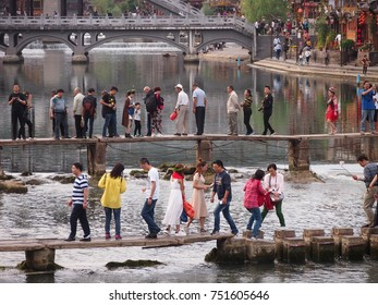 Fenghuang, China - 18 October, 2016: Tourists struggle to cross the narrow footbridge across the river in Fenghuang's old town. Many stop to take photos, just clogging up the bridge even more.