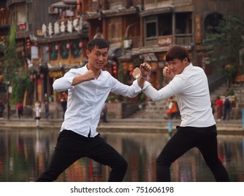 Fenghuang, China - 18 October, 2016: Two men pose on a narrow footbridge in the old town of Fenghuang. They pretend to be having a kung fu fight, causing a big queue of people behind them