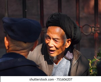 Fenghuang, China - 18 October, 2016: An elderly Chinese man chatting with friends in Fenghuang town square