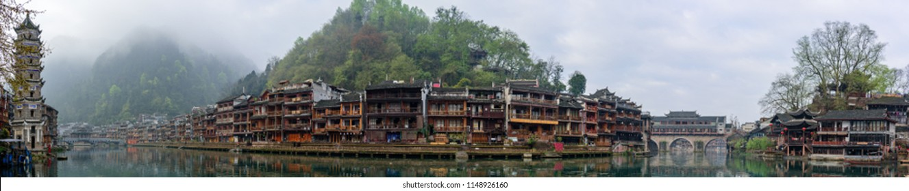 Fenghuang, China - 2018/03/26: Scenic traditional Chinese riverside buildings reflected in water of the Tuojiang River (Tuo Jiang River) in Phoenix Ancient Town (Fenghuang County).