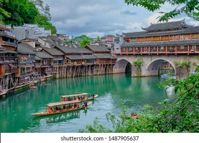 FENGHUANG, CHINA - APRIL 23, 2018: Chinese tourist attraction destination - Feng Huang Ancient Town (Phoenix Ancient Town) on Tuo Jiang River with bridge and tourist boat. Hunan Province, China