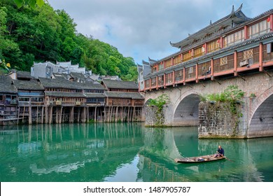 FENGHUANG, CHINA - APRIL 23, 2018: Unidentified chinese man in boat Feng Huang Ancient Town (Phoenix Ancient Town) on Tuo Jiang River with bridge and tourist boat. Hunan Province, China
