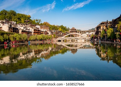 Fenghuang, China - November  2nd, 2019: Tourists walking along Phoenix Ancient Town (Fenghuang County). Awesome view of scenic old street. Fenghuang is a popular tourist destination of Asia.