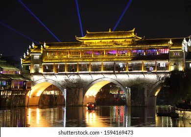 Fenghuang, China - November 3, 2019: At night, view of the river, the ancient bridge and its pagoda on the top