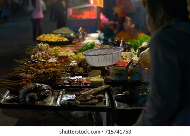 Fenghuang, China - September 12, 2007: A street stall vendor selling a variety of skewered food on trays at a night market