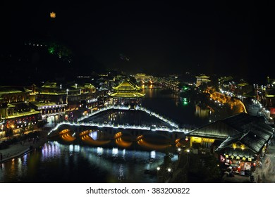 FENGHUANG, CHINA - SEPTEMBER 16, 2015: View of illuminated stone bridge over Tuo Jiang river and wooden houses in ancient town of Fenghuang known as Phoenix, China