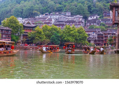 FENGHUANG, CHINA - SEPTEMBER 17, 2019: Tourist on wooden boat on the Tuojiang River in Phoenix Ancient Town (Fenghuang County), China. Fenghuang is regarded by UNESCO as a World Heritage Site.