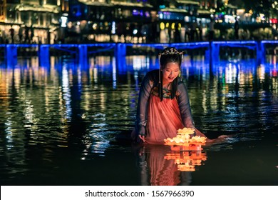 FENGHUANG, CHINA - SEPTEMBER 17, 2019: Local Chinese lady playing candle light on Tuojiang River in Phoenix Ancient Town (Fenghuang County), China. Fenghuang know as UNESCO as a World Heritage Site.