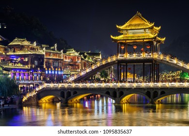 Fenghuang, China - September 22, 2017: Beautiful night view of scenic bridge over the Tuojiang River (Tuo Jiang River) in Phoenix Ancient Town. Tourists walking along amazing bridge.