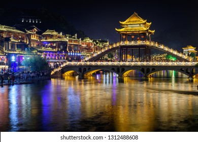 Fenghuang, China - September 22, 2017: Amazing night view of scenic bridge over the Tuojiang River (Tuo Jiang River) in Phoenix Ancient Town. Tourists walking along embankment and beautiful bridge.