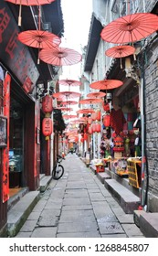 Fenghuang County, China - March 17, 2018. The narrow shopping street with decorated umbrella in tourist at Fenghuang Ancient Town (Phoenix ancient town), Hunan Province, China.