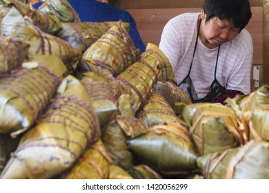 Fengjing, Shanghai/ China - 3rd June 2019: Women making and selling 'Zongzi' for Dragon Boat Festival. 'Zongzi' is a traditional food of glutinous rice and fillings wrapped in bamboo, tied with string
