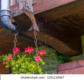 Fenilliaz, Aosta Valley, Italy - August 8, 2018: Exterior of a mountain house iwith geraniums in a copper pot and a spider web.