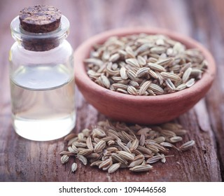 Fennel seeds with essential oil in a bottle on natural surface