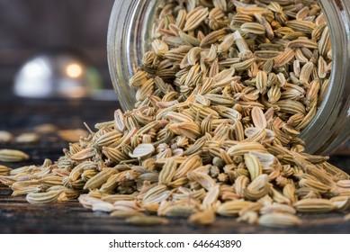 Fennel seeds spilled from spice jar
