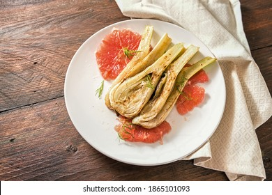 Sautéed fennel vegetable with grapefruit slices on a white plate and a rustic wooden table, homemade vegetarian snack, copy space, selected focus