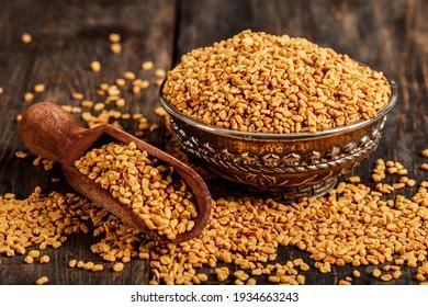 Fenugreek seeds on metal plate, spice, culinary ingredient. Fenugreek seeds in wooden spoon on textured background. Fenugreek seeds in a spoon and on a table.
