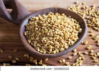 Fenugreek seeds on a wooden spoon