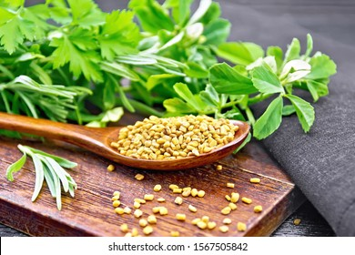 Fenugreek seeds in a spoon on a brown plate with herbs, dark napkin on wooden board background