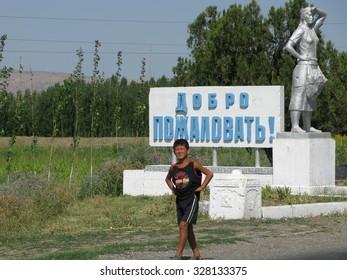 FERGANA, UZBEKISTAN - 23 JUL 2007: Unidentified Uzbeks boy walk on the street near Fergana city.