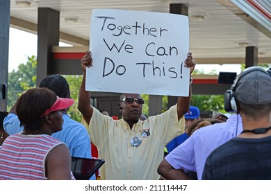 FERGUSON, MO/USA -  AUGUST 15, 2014: Man holds sign at the site of Quick Trip after Police Chief Thomas Jackson release of the name of the officer that shot Michael Brown.