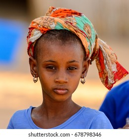 FERLO DESERT, SENEGAL - APR 25, 2017: Unidentified Fulani little girl in colored headscarf looks ahead. Fulanis (Peul) are the largest tribe in West African savannahs