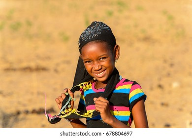 FERLO DESERT, SENEGAL - APR 25, 2017: Unidentified Fulani little girl in striped shirt and black headscarf smiles. Fulanis (Peul) are the largest tribe in West African savannahs