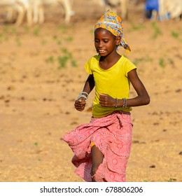 FERLO DESERT, SENEGAL - APR 25, 2017: Unidentified Fulani girl in yellow shirt and colored headscarf runs along the street. Fulanis (Peul) are the largest tribe in West African savannahs