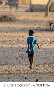 FERLO DESERT, SENEGAL - APR 25, 2017: Unidentified Fulani little boy plays on the street. Fulanis (Peul) are the largest tribe in West African savannahs