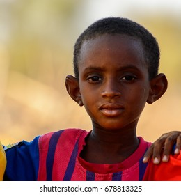 FERLO DESERT, SENEGAL - APR 25, 2017: Unidentified Fulani little boy in striped shirt looks ahead. Fulanis (Peul) are the largest tribe in West African savannahs