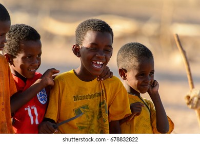 FERLO DESERT, SENEGAL - APR 25, 2017: Unidentified Fulani little boy in yellow shirt smiles. Fulanis (Peul) are the largest tribe in West African savannahs