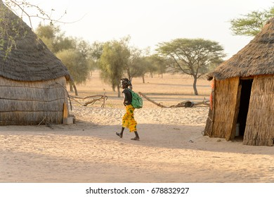 FERLO DESERT, SENEGAL - APR 25, 2017: Unidentified Fulani little girl in colored headscarf with backpack walks along the street. Fulanis (Peul) are the largest tribe in West African savannahs