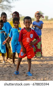 FERLO DESERT, SENEGAL - APR 25, 2017: Unidentified Fulani little boy in red suit puts his hand on a hip. Fulanis (Peul) are the largest tribe in West African savannahs